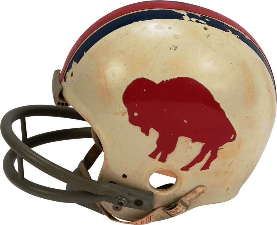 """1972 Dick Cunningham Buffalo Bills Game Worn Helmet This fantastic Buffalo Bills helmet was game worn by Dick Cunningham in 1972 and features the rare, standing buffalo style only used until 1973. The red standing buffalo stickers appear on both sides of the helmet, with red and blue stripes on top. The Riddell helmet has original """"water pack"""" padding inside. The number """"63"""" is written in marker inside the right ear piece, which was the number worn by Cunningham in '72. The helmet shows nice use with scuffs and bruises, and some of one of the blue stripes on top is chipped. There is a May 1972 manufacturer's sticker inside underneath the padding. Sold for: $1,250.40"""